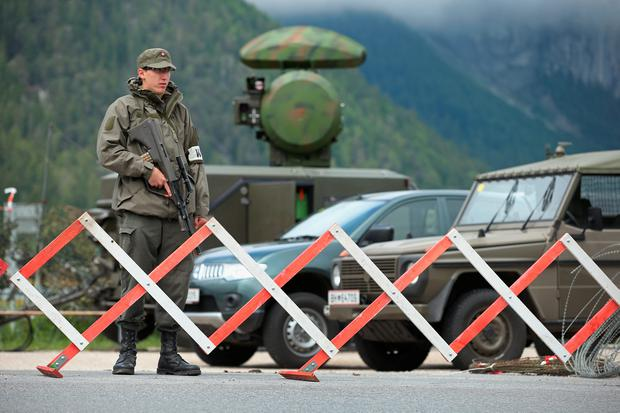 A soldier of the Austrian army stands next to a mobile radar station that is safeguarding the upcoming Bilderberg conference on June 9, 2015 near Telfs, Austria (Photo by Sean Gallup/Getty Images)