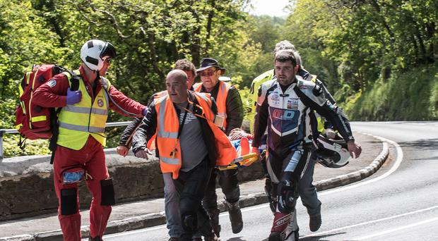 PACEMAKER BELFAST 09/06/2015 Michael Dunlop carries his brother William on a stretcher after his crash during practice on the island yesterday