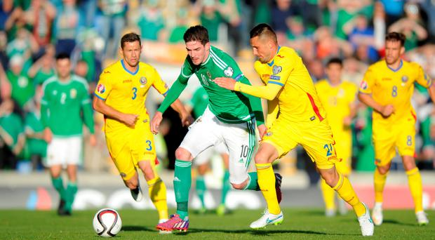 Northern Ireland's Kyle Lafferty and Romania's Dragos Grigore (right) battle for the ball during the UEFA European Championship Qualifying game at Windsor Park, Belfast. Martin Rickett/PA Wire.