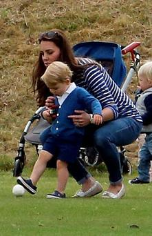 The Duchess of Cambridge with Prince George, as the Duke of Cambridge and Prince Harry take part in a charity polo match at Beaufort Polo Club in Tetbury, Gloucestershire. Steve Parsons/PA Wire.