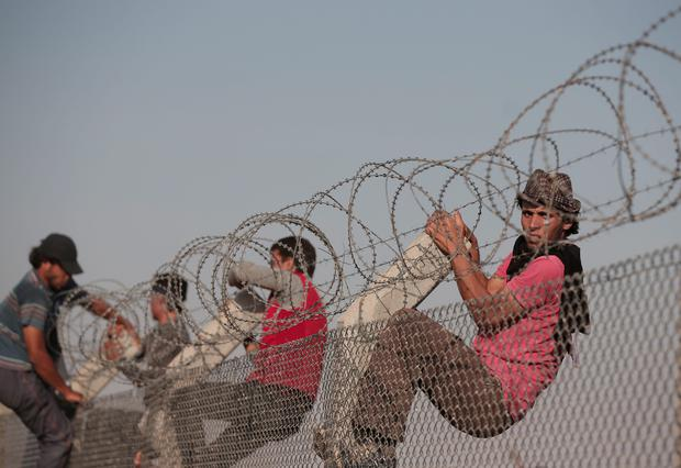 Syrian refugees climb over the barbed-wire border fence from Syria to Turkey in Akcakale, Sanliurfa province, southeastern Turkey, Sunday, June 14, 2015. The mass displacement of Syrians came as Kurdish fighters announced they are making headway toward the city of Tal Abyad, a stronghold of the extremist group near the Turkish border. The loss of Tal Abyad would be a major blow to the extremist group as the border town is a major avenue for commerce for the group.(AP Photo/Lefteris Pitarakis)