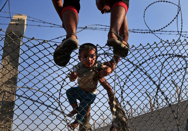 Syrian refugees carry a baby over the border fence into Turkey from Syria in Akcakale, Sanliurfa province, southeastern Turkey, Sunday, June 14, 2015. Thousands of Syrians cut through a border fence and crossed over into Turkey on Sunday, fleeing intense fighting in northern Syria between Kurdish fighters and jihadis.The flow of refugees came as Syrian Kurdish fighters closed in on the outskirts of a strategic Islamic State-held town on the Turkish border. (AP Photo/Lefteris Pitarakis)