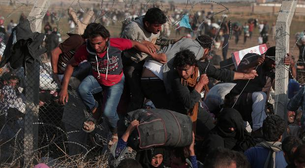 Syrian refugees cross into Turkey from Syria after breaking the border fence in Akcakale, Sanliurfa province, southeastern Turkey, Sunday, June 14, 2015. Thousands of Syrians cut through a border fence and crossed over into Turkey on Sunday, fleeing intense fighting in northern Syria between Kurdish fighters and jihadis.The flow of refugees came as Syrian Kurdish fighters closed in on the outskirts of a strategic Islamic State-held town on the Turkish border. (AP Photo/Lefteris Pitarakis)