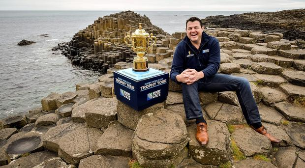 Giant aim: former Ireland international Reggie Corrigan gets up close and personal with the Webb Ellis Trophy at the Giant's Causeway as part of trophy's pre-World Cup tour