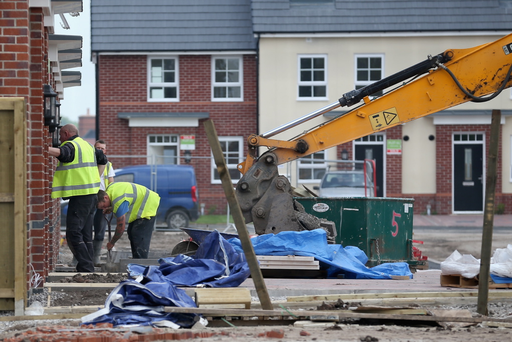 Construction workers build new houses on a housing development