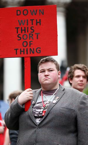 A demonstrator holds a placard as he waits for the start of protest