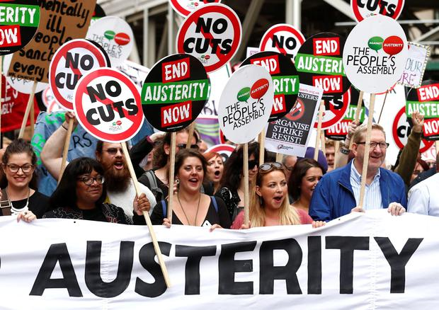 Demonstrators including Labour MP Diane Abbott (2L), British singer Charlotte Church (C) and General Secretary of Unite Len McCluskey (2) hold a banner as they march to protest against the British government's spending cuts and austerity measures in London. AFP/Getty Images