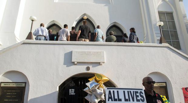 Demonstrators stand in front of a memorial and a line of people lined up to enter the Emanuel AME Church before a worship service. (AP Photo/Stephen B. Morton)