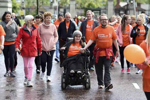 Sports Minister Caral Ni Chuilin (fourth from left) is among hundreds of people joining Michaela Hollywood (centre) as she completes the final mile of her marathon at Stormont yesterday