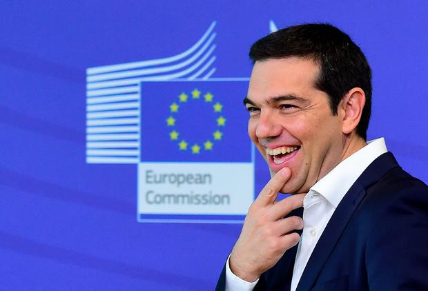 Greece's Prime Minister Alexis Tsipras laughs as he welcomed by the European Commission president ahead of an emergency summit with the leaders of Athens' creditors at the European Commission in Brussels, on June 22, 2015.