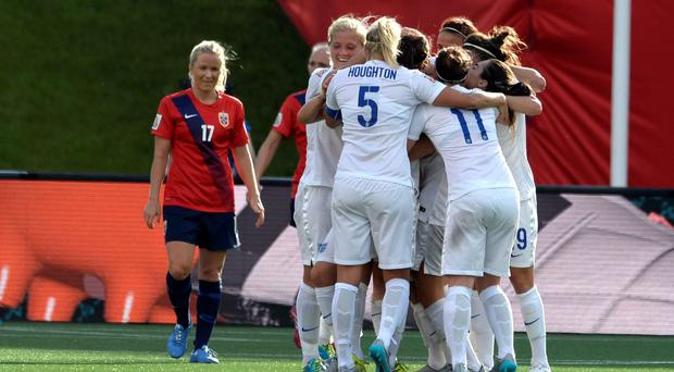 English players embrace following a goal by Lucy Bronze