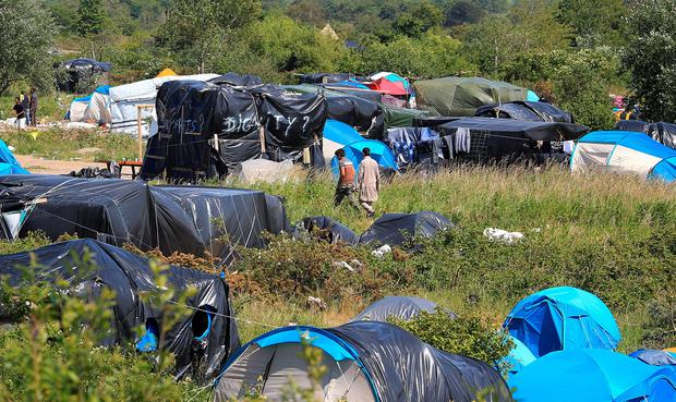 Migrants camp in squalid conditions on a dusty site dubbed