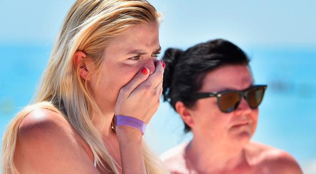 SOUSSE, TUNISIA - JUNE 27: A woman grieves as she lay flowers at the beach next to the Imperial Marhaba Hotel where 38 people were killed yesterday in a terrorist attack on June 27, 2015 in Souuse,Tunisia. Habib Essid Prime Minister of Tunisia announced a clampdown on security after the attack on a holiday resort.. (Photo by Jeff J Mitchell/Getty Images)