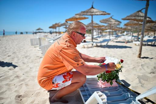 SOUSSE, TUNISIA - JUNE 27: A man places flowers at the beach next to the Imperial Marhaba Hotel where 38 people were killed yesterday in a terrorist attack on June 27, 2015 in Souuse,Tunisia. Habib Essid Prime Minister of Tunisia announced a clampdown on security after the attack on a holiday resort.. (Photo by Jeff J Mitchell/Getty Images)