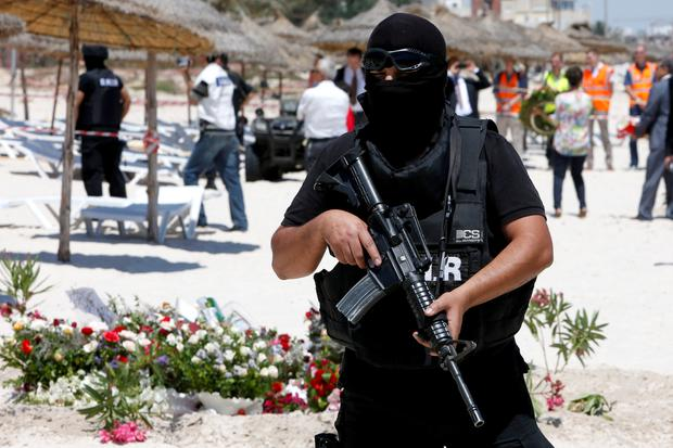A hooded Tunisian police officer stands guard at the scene of Friday's beach massacre