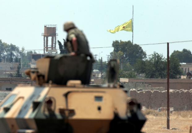 In this photo taken from the Turkish side of the border between Turkey and Syria, in Akcakale, southeastern Turkey, a Turkish soldier on an armoured personnel carrier watches as in the background a flag of the Kurdish People's Protection Units, or YPG, is raised over the city of Tal Abyad, Syria, Tuesday, June 16, 2015. (AP Photo/Lefteris Pitarakis)