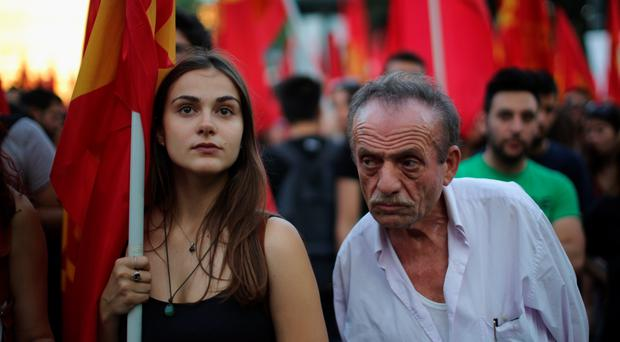 Greek Communist Party supporters listen to speeches during a rally in Syntagma Square near the Parliament on July 2, 2015 in Athens, Greece. As people continue to queue outside banks Greek finance minister Yanis Varoufakis said that he will quit if voters don't back him up in Sunday's referendum. (Photo by Christopher Furlong/Getty Images)
