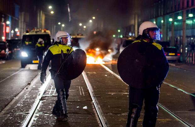 Anti riot police forces patrol in the Schilderswijk district of The Hague, in the early hours of July 2, 2015, after protesters have gathered for the third night in a row following the death of Mitch Henriquez, a 42 year old Aruban man who died on 28 June in hospital after being arrested at a music festival in the city on 27 June. AFP/Getty Images