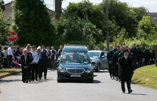 The coffin of mother-of-two Lorna Carty, a victim of the Tunisia terror attack is carried in a hearse, escorted by players from Meath GAA and Dunderry GAA, from the Church of the Assumption Robinstown, Co Meath. Niall Carson/PA Wire