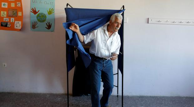 A man casts his vote at polling station in Athens, Sunday, July 5. (AP Photo/Thanassis Stavrakis)