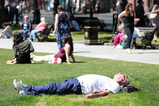 Members of the public enjoying the recent warm weather at Belfast City Hall. Pic: Kelvin Boyes / Press Eye.