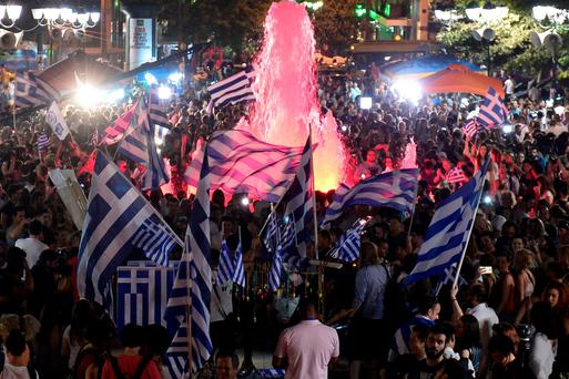 People celebrate in Athens after Sunday's referendum