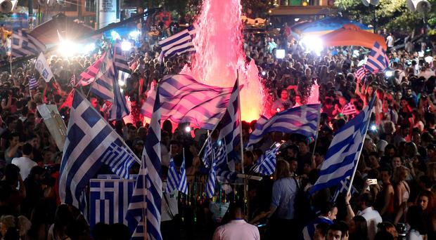 People celebrate in Athens on July 5, 2015 after the first exit-polls of the Greek referendum. Over 60 percent of Greeks rejected further austerity dictated by the country's EU-IMF creditors in a referendum, results from 20 percent of polling stations showed. AFP PHOTO / LOUISA GOULIAMAKILOUISA GOULIAMAKI/AFP/Getty Images
