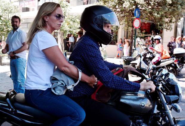 Outgoing Greek Finance minister Yanis Varoufakis leaves onto his motorcycle with his wife Danai after his resignation at the ministry of Finance in downtown Athens on July 6 2015. AFP/Getty Images