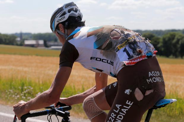 Belgium's Johan Van Summeren continues the race with his torn jersey after crashing with several other riders during the third stage of the Tour de France cycling race over 159.5 kilometers (99.1 miles) with start in Antwerp and finish in Huy, Belgium, Monday, July 6, 2015. (AP Photo/Christophe Ena)