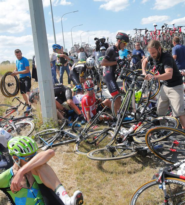 Several riders lie on the road after crashing during the third stage of the Tour de France cycling race over 159.5 kilometers (99.1 miles) with start in Antwerp and finish in Huy, Belgium, Monday, July 6, 2015. (AP Photo/Christophe Ena)