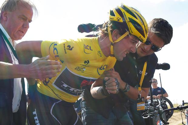 Switzerland's Fabian Cancellara, wearing the overall leader's yellow jersey, is treated for a back injury after crashing with several other riders during the third stage of the Tour de France cycling race over 159.5 kilometers (99.1 miles) with start in Antwerp and finish in Huy, Belgium, Monday, July 6, 2015. (AP Photo/Christophe Ena)