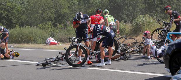 Portugal's Rui Costa, right in white, and Laurens ten Dam of the Netherlands, left, lie on the road as other riders get up after crashing during the third stage of the Tour de France cycling race over 159.5 kilometers (99.1 miles) with start in Antwerp and finish in Huy, Belgium, Monday, July 6, 2015. (AP Photo/Christophe Ena)