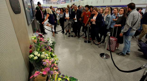 People look at flowers left at Kings Cross Underground station in London, as Britain remembers the July 7 attacks amid a welter of warnings about the enduring and changing threat from terrorism a decade on. Chris Radburn/PA Wire