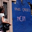 A woman walks past a slogan written on a wall in Athens on July 7, 2015. AFP/Getty Images
