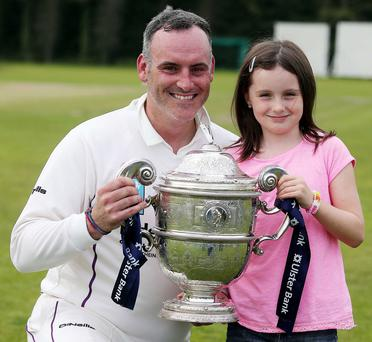 Pride and joy: Neil Russell and his daughter Evie lift the league title after Inst were crowned champions last year PRESSEYE
