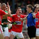 Outcry: Cork surround Paudie Hughes after Kerry are given a pivotal penalty in the Munster final