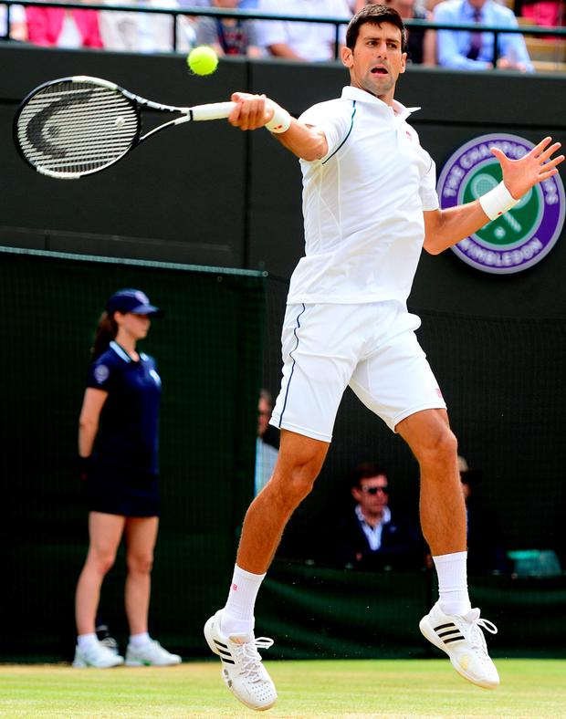 Marathon man: Novak Djokovic returns a serve during his thrilling five-set victory over Kevin Anderson at Wimbledon
