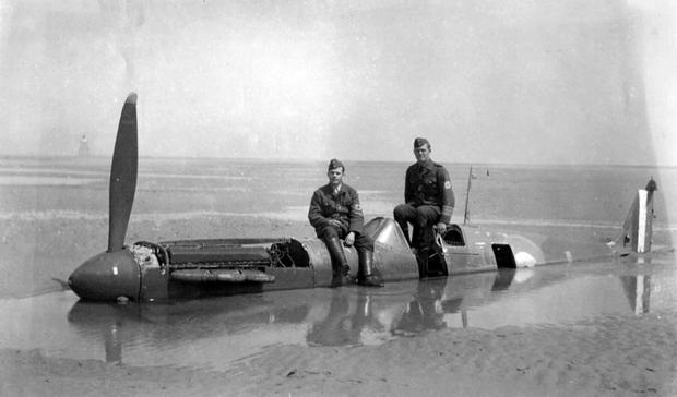 Undated handout file photo issued by Christie's of German soldiers sitting on the fuselage of a downed Spitfire on the Calais coast, as the restored plane has sold for a record price at auction - with the multi-million-pound profits donated to charity