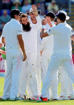 Howzat: England's Moeen Ali is mobbed by team-mates after taking the wicket of Australia captain Michael Clarke