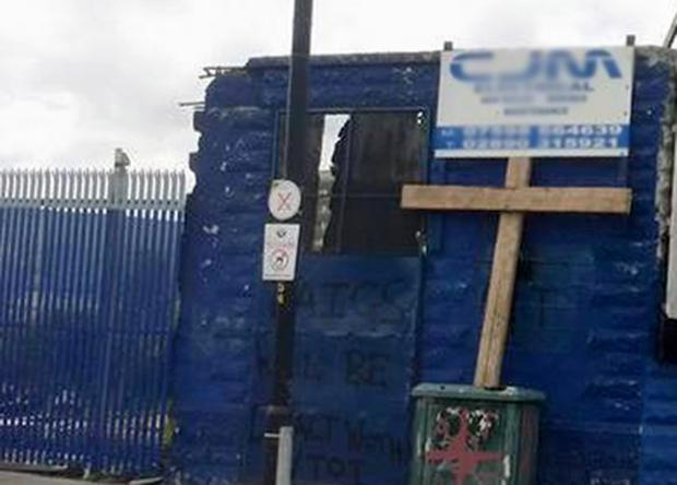 A wooden cross on the Donegall Road next to the message 'taigs will be dealt with, VTOT'