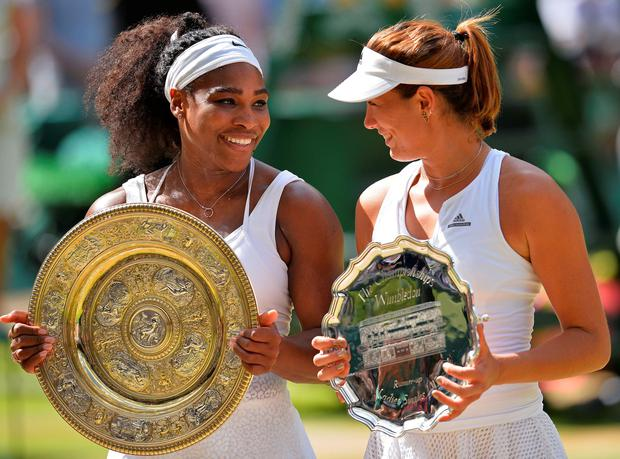 US player Serena Williams (L) holds the winner's trophy, the Venus Rosewater Dish, next to Spain's Garbine Muguruza (R) with the runners up shield. AFP/Getty Images