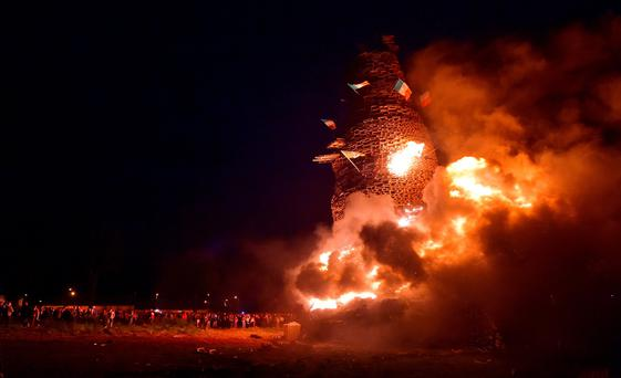 Hundreds of people gather for the Eleventh Night bonfire at the New Mossley housing estate near Belfast. New Mossley is widely recognised as the largest bonfire in the province. (Photo by Charles McQuillan/Getty Images)