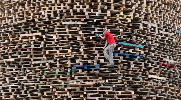 A bonfire builder at work in the New Mosley area of Belfast. Niall Carson/PA Wire.