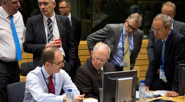 German Finance Minister Wolfgang Schaeuble, sitting center, goes over papers with members of his delegation during a round table meeting of eurogroup finance ministers at the EU Lex building in Brussels on Sunday, July 12, 2015.