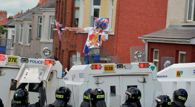 BELFAST, NORTHERN IRELAND - JULY 13: A Loyalist breaks through a police barrier and taunts police officers as Orangemen are prevented from progressing on the return journey towards the controversial Ardoyne flashpoint the Twelfth of July parade on July 13, 2015 in Belfast, Northern Ireland. (Photo by Charles McQuillan/Getty Images)