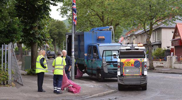 Members of Belfast City Council performing a cleanup on the Woodvale Road and Crumlin Road junction where police were attacked with bricks, bottles in north Belfast. Photo Arthur Allison/Pacemaker Press
