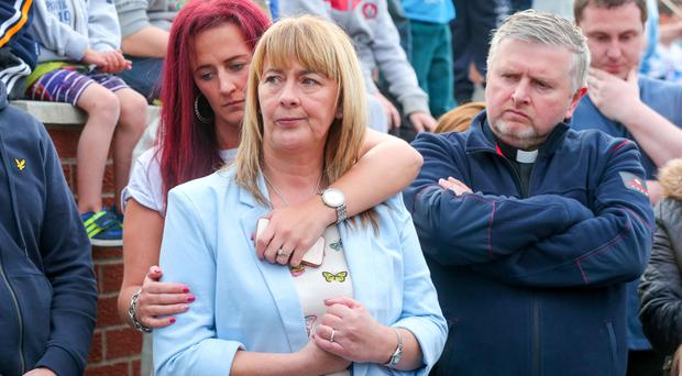 Phoebe Clawson's aunt Patricia McAuley, who spoke at last night's vigil, being hugged by one of Phoebe's sisters and supported by Fr Gary Donegan