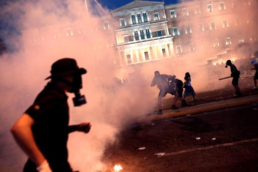 A protester clashes with riot police in front of the Greek Parliament in Athens on July 15, 2015. Anti-austerity protesters hurled petrol bombs at police in front of Greece's parliament on July 15, as lawmakers began debating deeply unpopular reforms needed to unlock a new eurozone bailout. Riot police responded with tear gas against dozens of hooded protesters who set ablaze parts of Syntagma square in central Athens. AFP PHOTO / ANGELOS TZORTZINISANGELOS TZORTZINIS/AFP/Getty Images