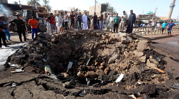 Iraqi men look at a crater left by a massive suicide car bomb attack carried out the previous day by the Islamic State group in the predominantly Shiite town of Khan Bani Saad, 20 km north of Baghdad, on July 18, 2015