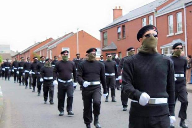 Dozens of masked men and women marched through Londonderry today during the funeral of veteran republican Peggy O'Hara.